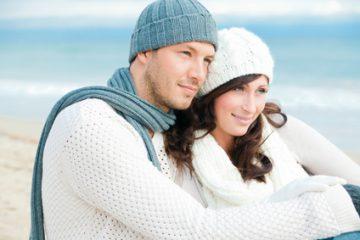 Verliebts Paar sitzt zusammen am Strand