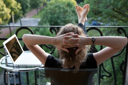 Frau sitzt auf eineme Balkon